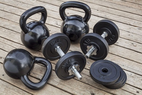 Kettlebells and Dumbbells Displayed on a Patio