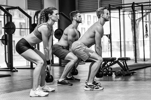 Three People Doing Kettlebell Training