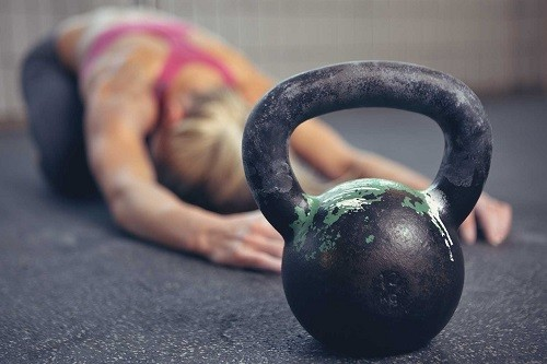 Woman Stretching Behing Kettlebell